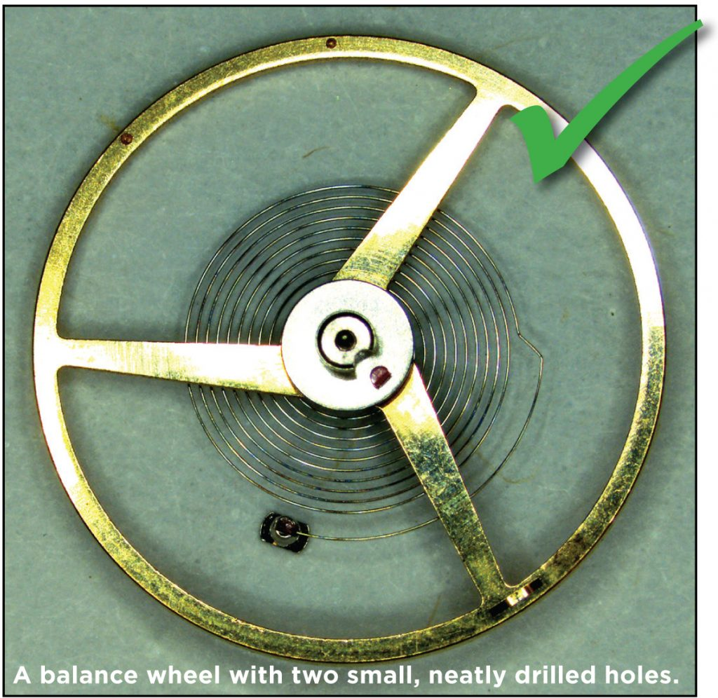 A balance wheel with two small, neatly drilled holes.