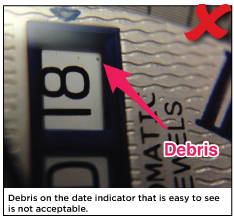 Debris on the date indicator that is easy to see is not acceptable.