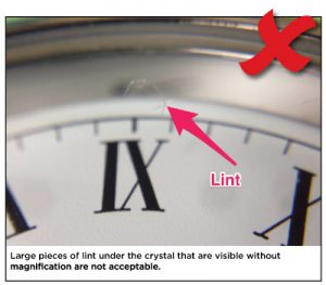 Large pieces of lint under the crystal that are visible without magnification are not acceptable.